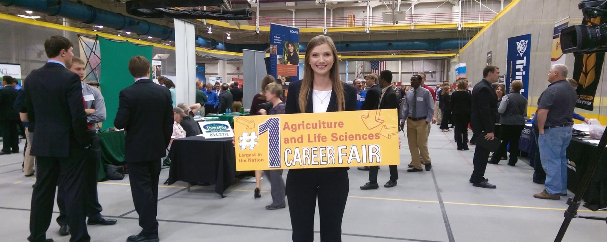 Student at career fair holding a sign that says: Largest in the nation #1 Agriculture and Life Sciences Career Fair